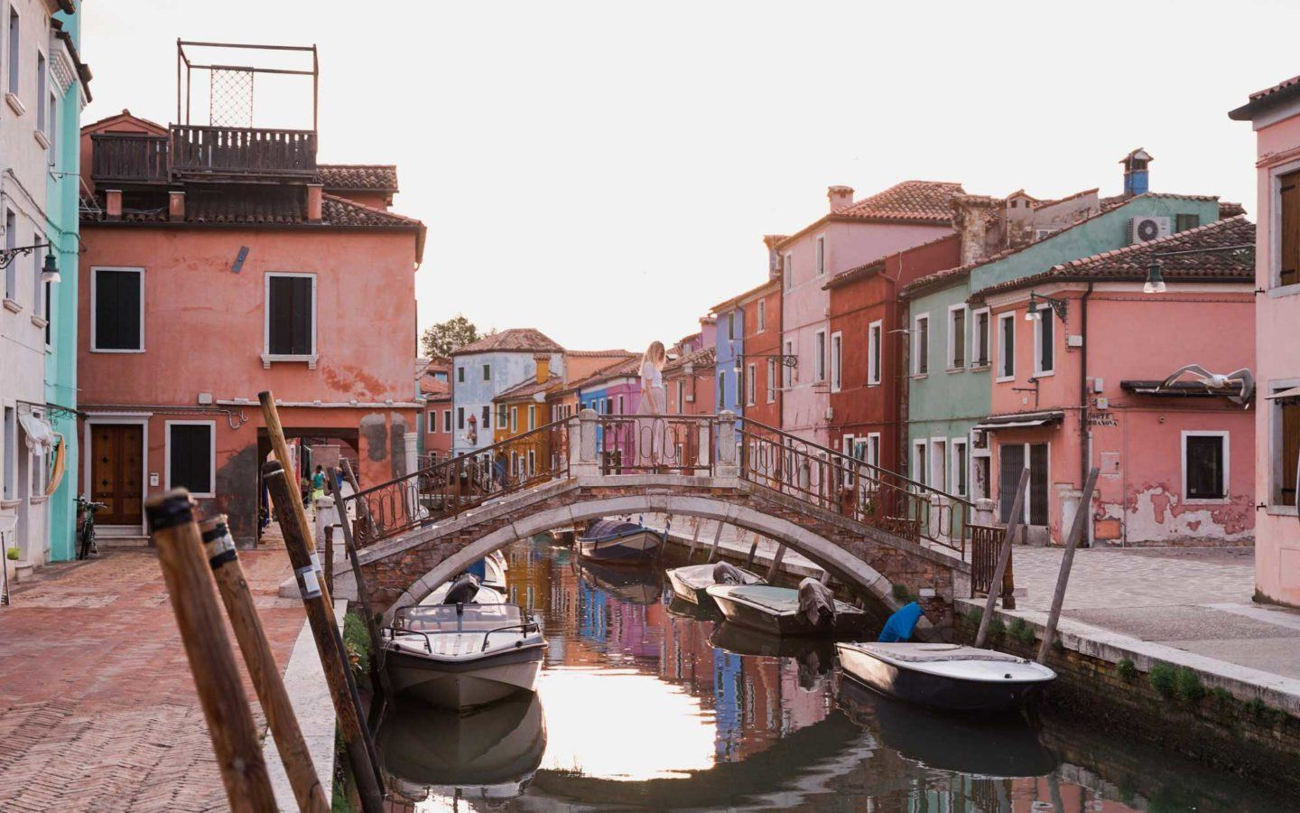 canal on burano island in venice with boats parked along the side and a bridge crossing