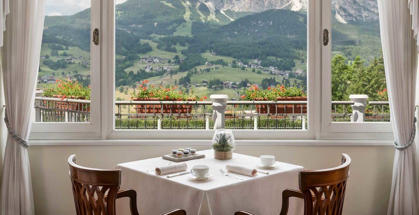 set table with two chairs sitting in front of window overlooking mountains