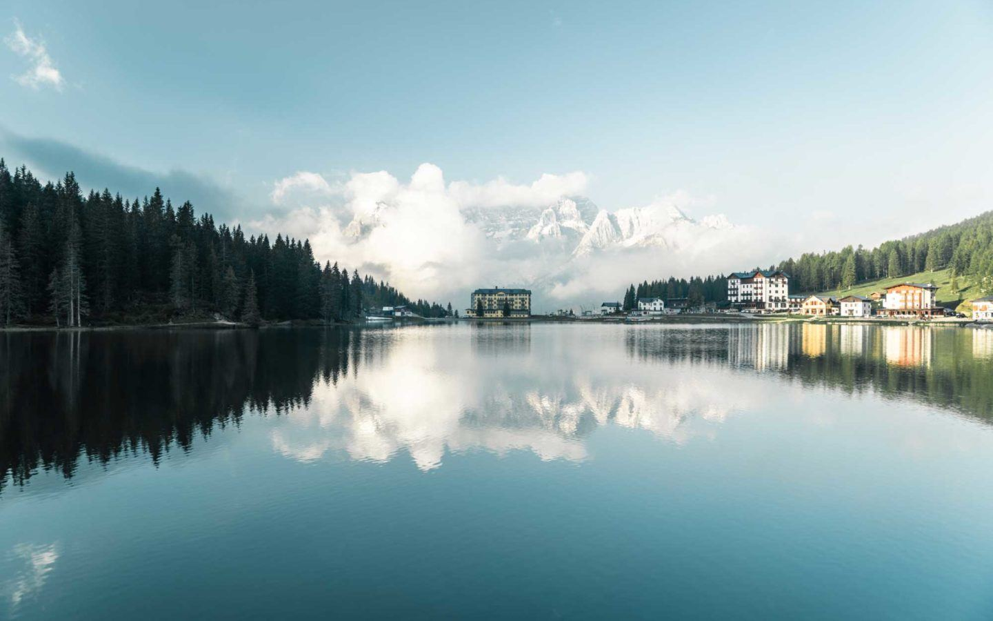 huge lake in cortina with trees mountains and clouds reflected in the water