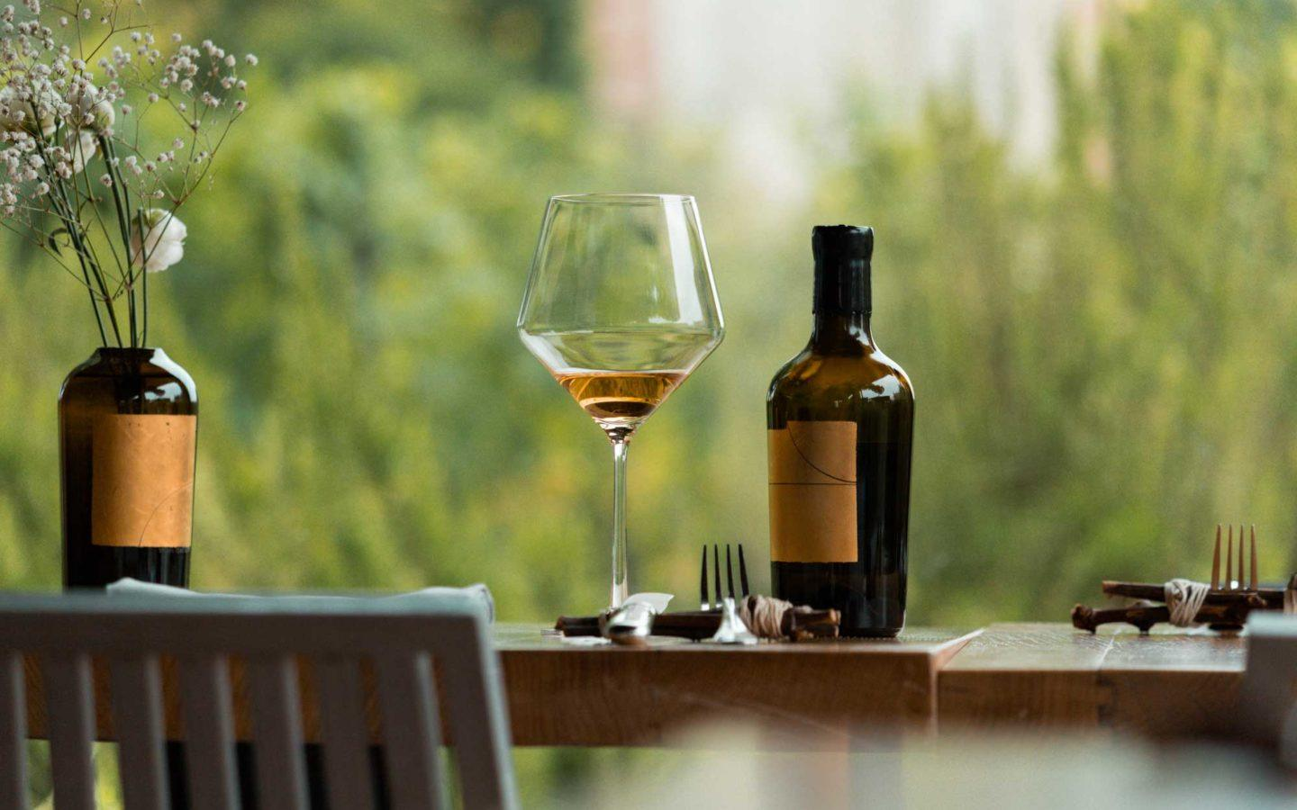 glass and bottle of wine sitting on wooden table